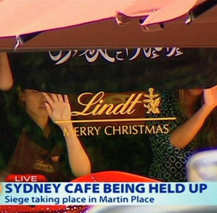 This image taken from video shows people holding up what appeared to be a black flag with white Arabic writing on it, inside a cafe in Sydney, Australia Monday, Dec. 15, 2014