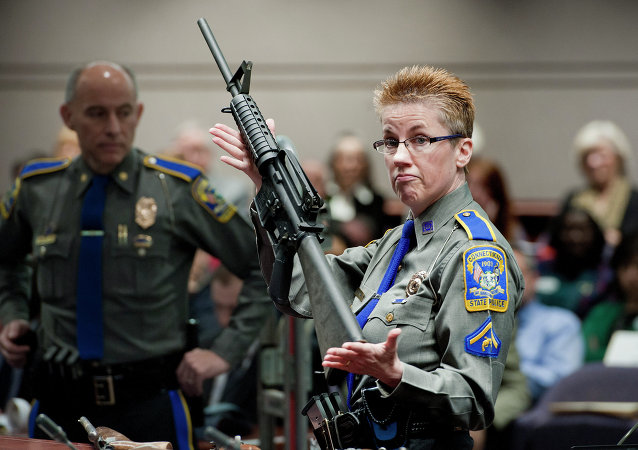 In this Jan. 28, 2013, file photo, firearms training unit Detective Barbara J. Mattson, of the Connecticut State Police, holds up a Bushmaster AR-15 rifle, the same make and model of gun used by Adam Lanza in the Sandy Hook School shooting, for a demonstration during a hearing of a legislative subcommittee reviewing gun laws, at the Legislative Office Building in Hartford, Connecticut.