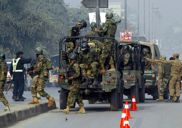 Pakistani army troops arrive to conduct an operation at a school under attack by Taliban gunmen in Peshawar, Pakistan, Tuesday, Dec. 16, 2014