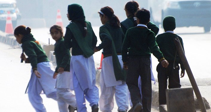 Schoolchildren cross a road as they move away from a military run school that is under attack by Taliban gunmen in Peshawar, December 16, 2014