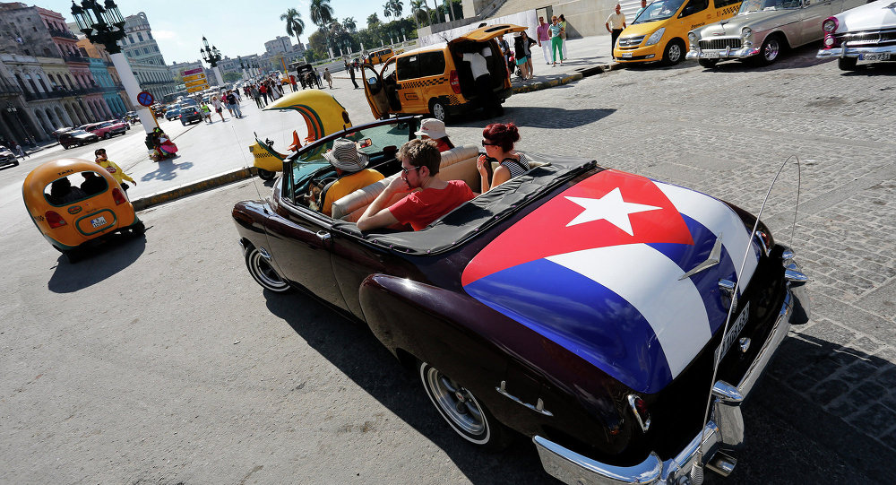 Tourists take a ride in a classic American convertible car with the Cuban national flag