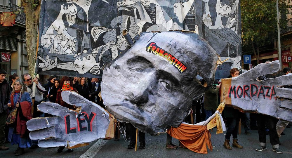 Demonstrators hold a banner featuring a painting of Pablo Picaso's The Guernica (back) and a cut-out of former Spanish dictator Francisco Franco (C), during a protest against the Spanish government's new anti-protest security law in Barcelona December 20, 2014.
