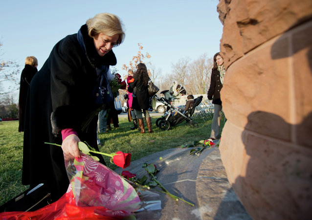 Mary Kay Stratis lays flowers for her husband Elia Stratis, as relatives and friends of the bombing victims gather around the memorial cairn at Arlington National Cemetery, in Arlington, Va., Sunday, Dec. 21, 2014