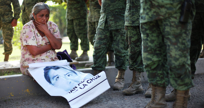 In this Dec. 18, 2014 photo, a woman who identified herself as the mother of missing student Adan Abarajan de la Cruz, 23, sits next to Mexican army soldiers standing in front of the entrance to the 27th Infantry Battalion base in Iguala, Mexico