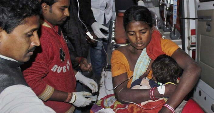 In this Tuesday, Dec. 23, 2014 photo, an injured woman and her child are carried in an ambulance to a local hospital in Sonitpur district in India's northeast state of Assam, India