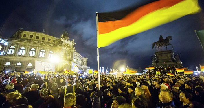 Participants hold German national flags during a demonstration organised by anti-immigration group PEGIDA  outside Semperoper opera house in Dresden December 22, 2014