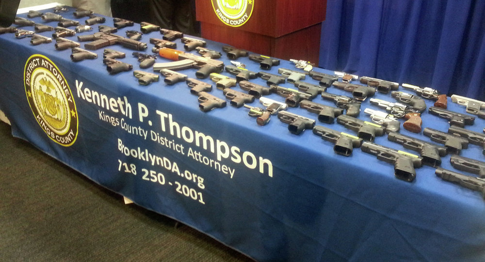 A collection of handguns and two assault rifles fill a table during a news conference at the Brooklyn District attorney's Office, Tuesday, Dec. 23, 2014