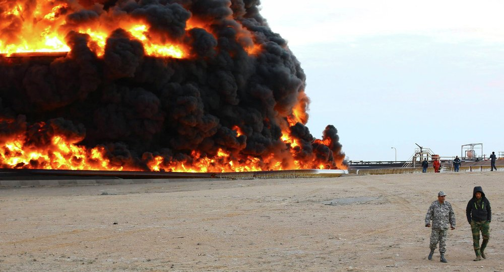 Firefighters try to put out the fire in an oil tank in Es Sider port December 26, 2014