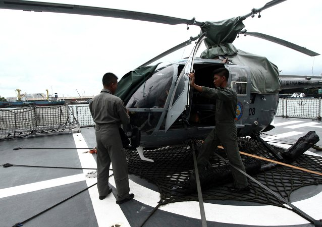 Navy soldiers check an helicopter on the deck of KRI Sultan Hasanuddin-366 warship before joining in search operations for AirAsia flight QZ8501 at Batuampar port in Batam, December 29, 2014