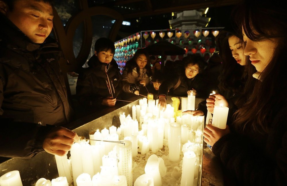 Buddhists light candles during New Year celebrations at Jogye Buddhist temple in Seoul, South Korea, Thursday, Jan. 1, 2015