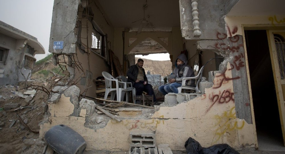 Palestinians sit in a room of their war-damaged house in the Shijaiyah neighborhood of Gaza City, Tuesday, Jan. 6, 2015