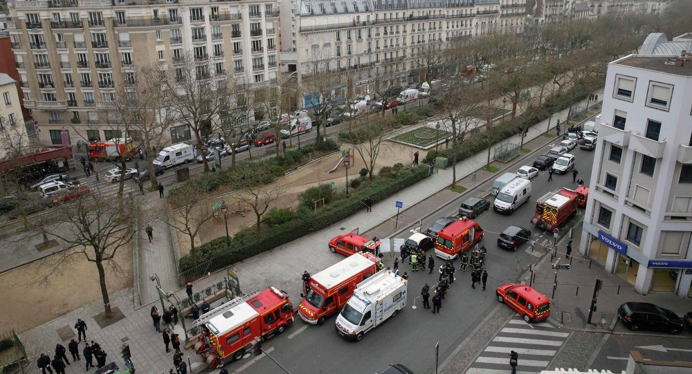 Police and rescue forces are seen near the scene after a shooting at the Paris offices of Charlie Hebdo, a satirical newspaper, January 7, 2015