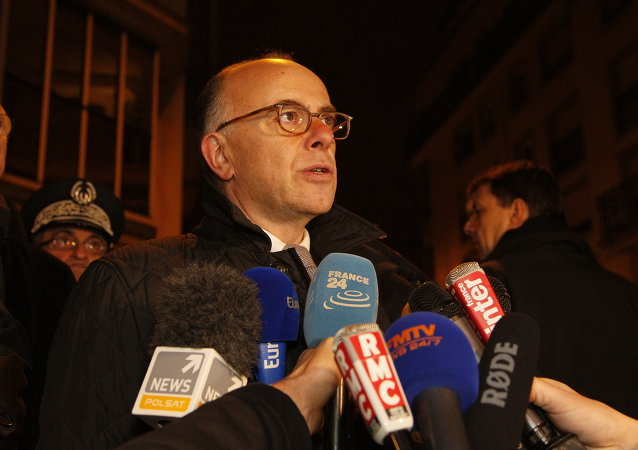 French Interior Minister Bernard Cazeneuve speaks to journalists, near the offices of the satirical weekly Charlie Hebdo, on January 7, 2015
