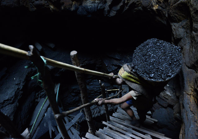 In this photograph taken on January 31, 2013, a miner slowly carries a heavy load of wet coal on a basket hundreds of feet up on wooden slats that brace the sides of a deep coal mine shaft near Rymbai village in the Indian northeastern state of Meghalaya. Millions of coal miners in India late January 7 have called off a five-day strike on the second day after a lengthy meeting with the government, averting power cuts in the energy-hungry country.
