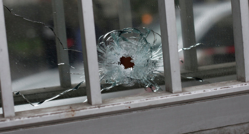 A bullet impact is seen in a window