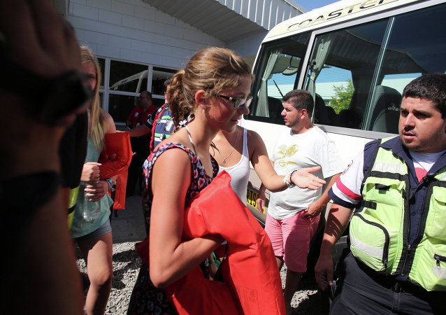 Tourists who were rescued after a catamaran sank off the Pacific coast of Costa Rica are escorted from a Coast Guard station into a bus, in the port of Caldera, Costa Rica, Thursday, Jan. 8, 2015