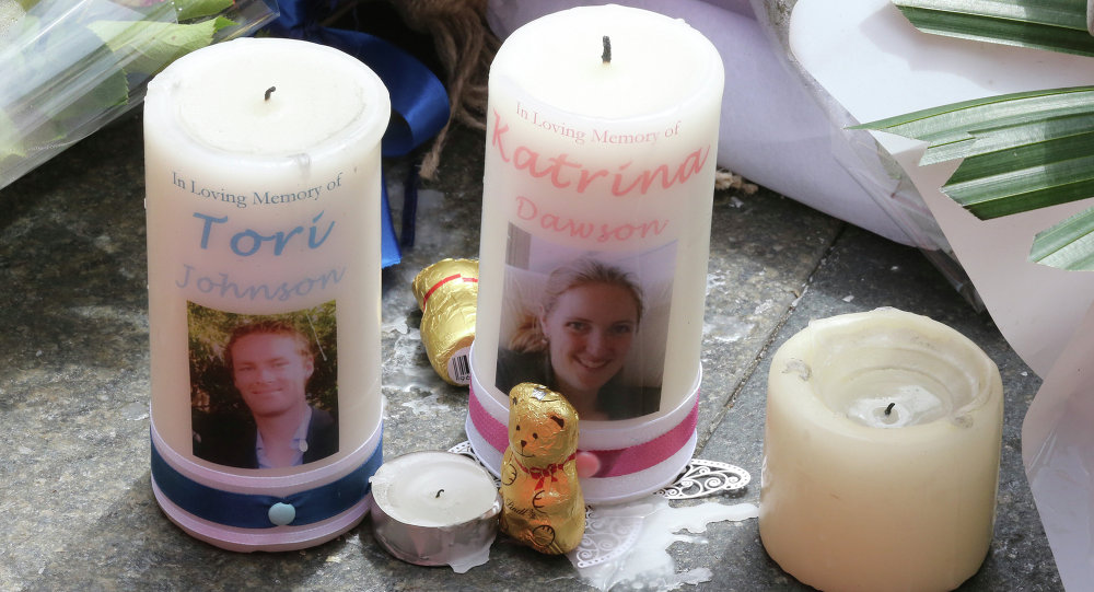 Two candle tributes with photos of siege victims Tori Johnson left, and Katrina Dawson are seen at a temporary memorial site close to the Lindt cafe in the central business district of Sydney, Australia
