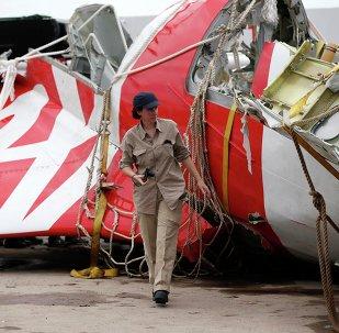 An Airbus investigator walks near part of the tail of the AirAsia QZ8501 passenger plane in Kumai Port, near Pangkalan Bun, Central Kalimantan January 12, 2015.