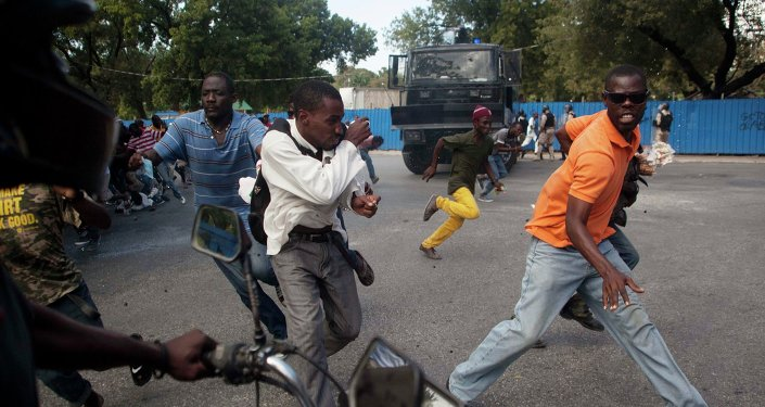 Demonstrators run during a protest demanding the resignation of President Michel Martelly in Port-au-Prince