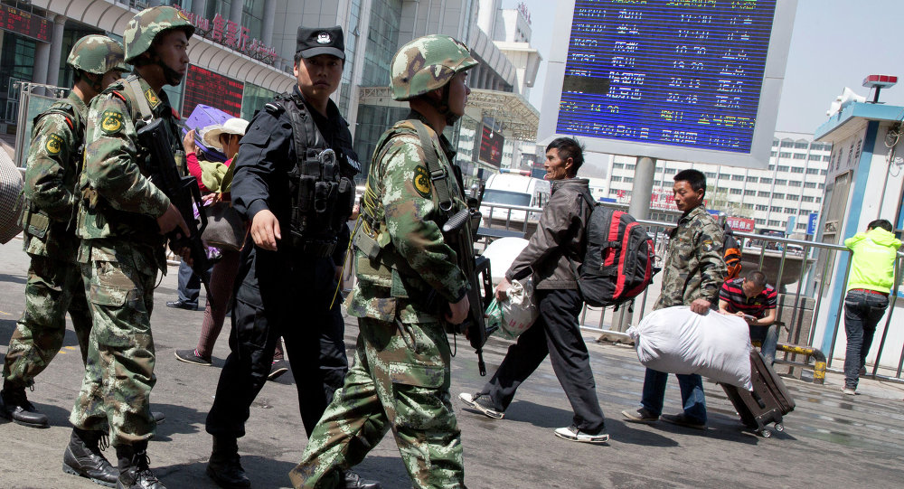 Armed Chinese paramilitary policemen march past the site of the explosion outside the Urumqi South Railway Station in Urumqi in northwest China's Xinjiang Uygur Autonomous Region, 2015.