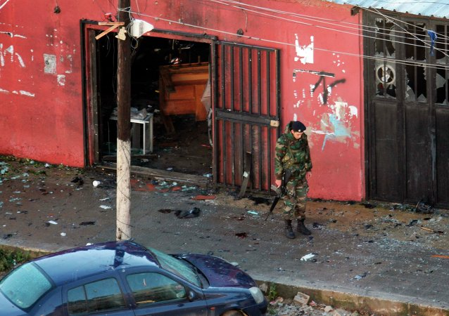 A Lebanese Army soldier guards a cafe where a suicide bomb attack took place in Jabal Mohsen, Tripoli January 11, 2015