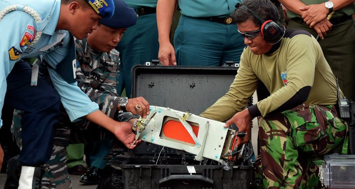 The flight data recorder of AirAsia QZ8501 is lifted out of a carrying case at the airbase in Pangkalan Bun, Central Kalimantan January 12, 2015