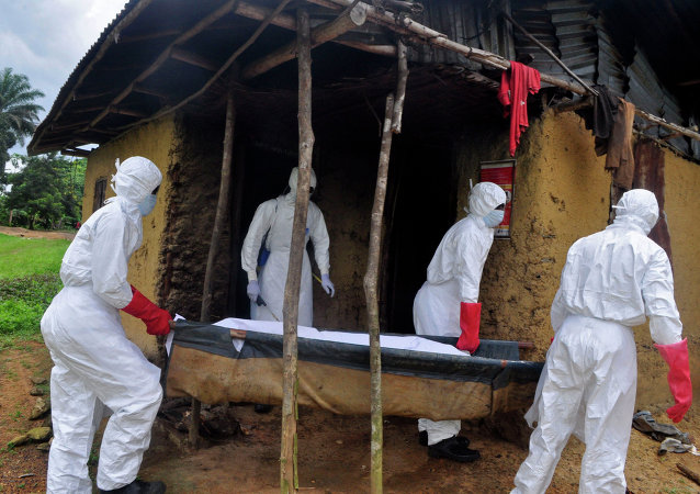 Hearth workers carry the body of a old man from his house as he is suspected of dying from the Ebola virus in the Siah Town area on the outskirts of Monrovia, Liberia