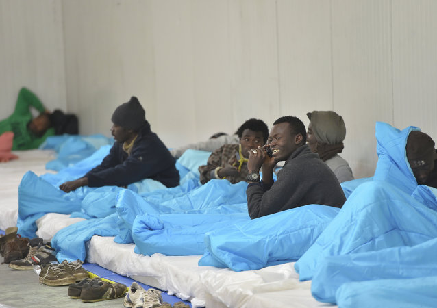 Migrants bed down for the night at a warehouse in Calais, northern France