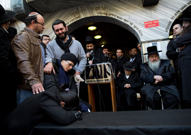 Family and relatives of French Jew Yoav Hattab, a victim of the attack on kosher grocery store in Paris, gather around a symbolic coffin for his funeral procession in the city of Bnei Brak near Tel Aviv, Israel, Tuesday, Jan. 13, 2015. Israel geared up on Tuesday for the solemn funerals of four Jewish victims of a Paris terror attack on a kosher supermarket amid rising concerns over increased anti-Semitism in Europe. Hattab will be buried in Jerusalem along with other victims of the attack.