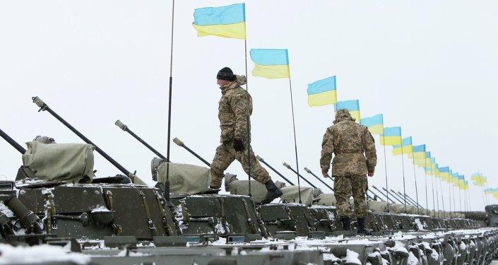 Ukrainian servicemen walk on armoured personnel carriers (APC)