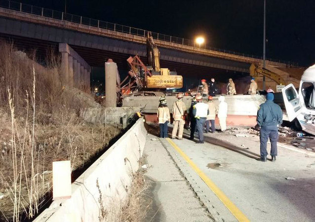 Workers stand near the scene following a highway overpass collapse in Cincinnati