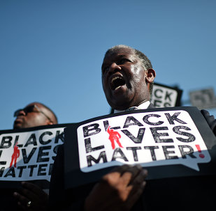 Men holding signs reading Black Lives Matter march in the 30th annual Kingdom Day Parade in honor of Dr. Martin Luther King Jr.
