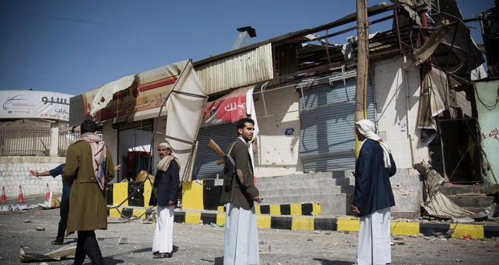 Houthi Shiite Yemeni stand guard in front of a building damaged during recent clashes near the presidential palace in Sanaa, Yemen, Tuesday, Jan. 20, 2015.