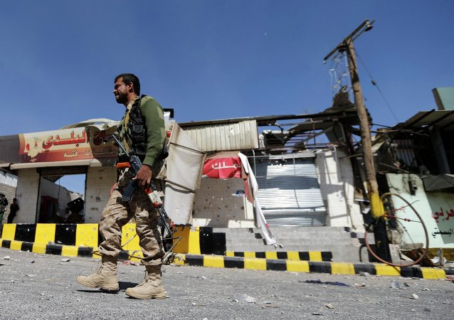 A Houthi fighter walks past damaged shops outside a Presidential Guards barracks on a mountain overlooking Presidential Palace in Sanaa January 20, 2015