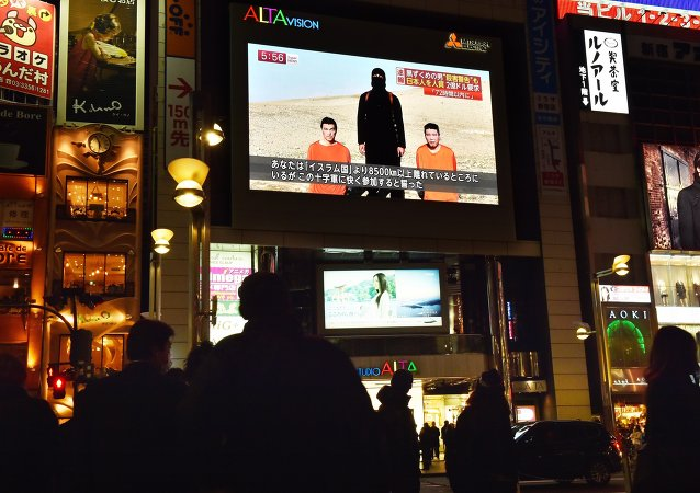 People look at a large TV screen in Tokyo on January 20, 2015 showing news reports about two Japanese men (in orange) who have been kidnapped by the Islamic State group