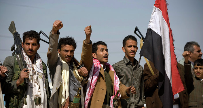 Houthi Shiite Yemenis raise their fists during clashes near the presidential palace in Sanaa, Yemen