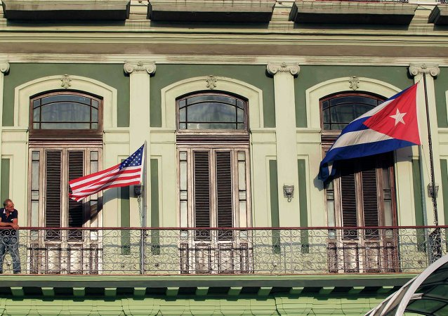 A man stands near the national flags of the US and Cuba (R) on the balcony of a hotel being used by the first U.S. congressional delegation to Cuba since the change of policy announced by US President Barack Obama on December 17, in Havana.