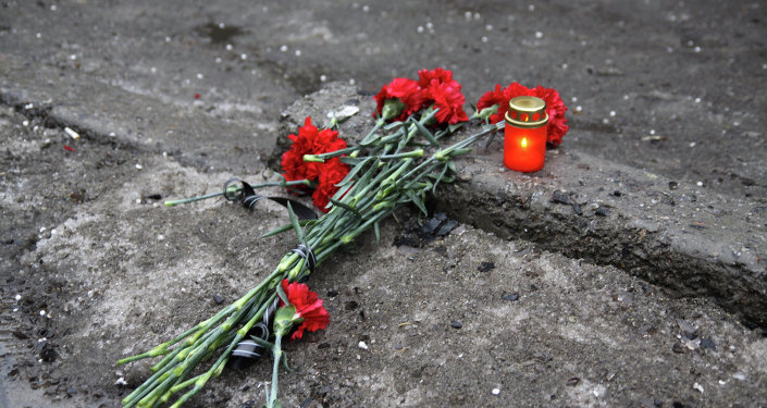 A candle and flowers are layed at a bus stop where 13 people were killed in a trolleybus shelling in Donetsk, eastern Ukraine, on January 22, 2015