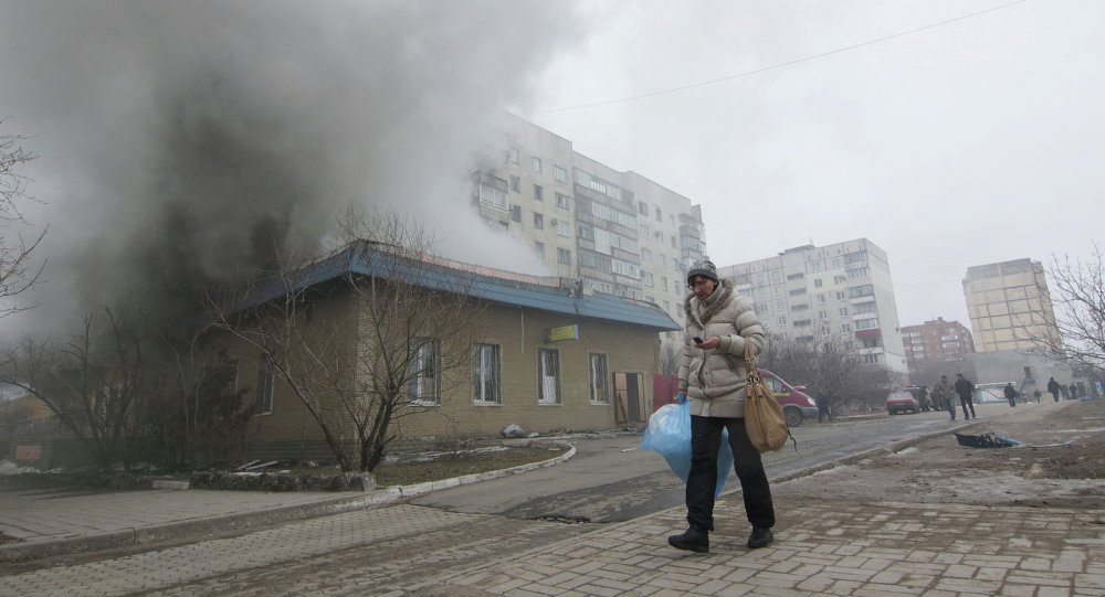 A woman resident passes by a burning house in Mariupol, Ukraine, Saturday, Jan. 24, 2015