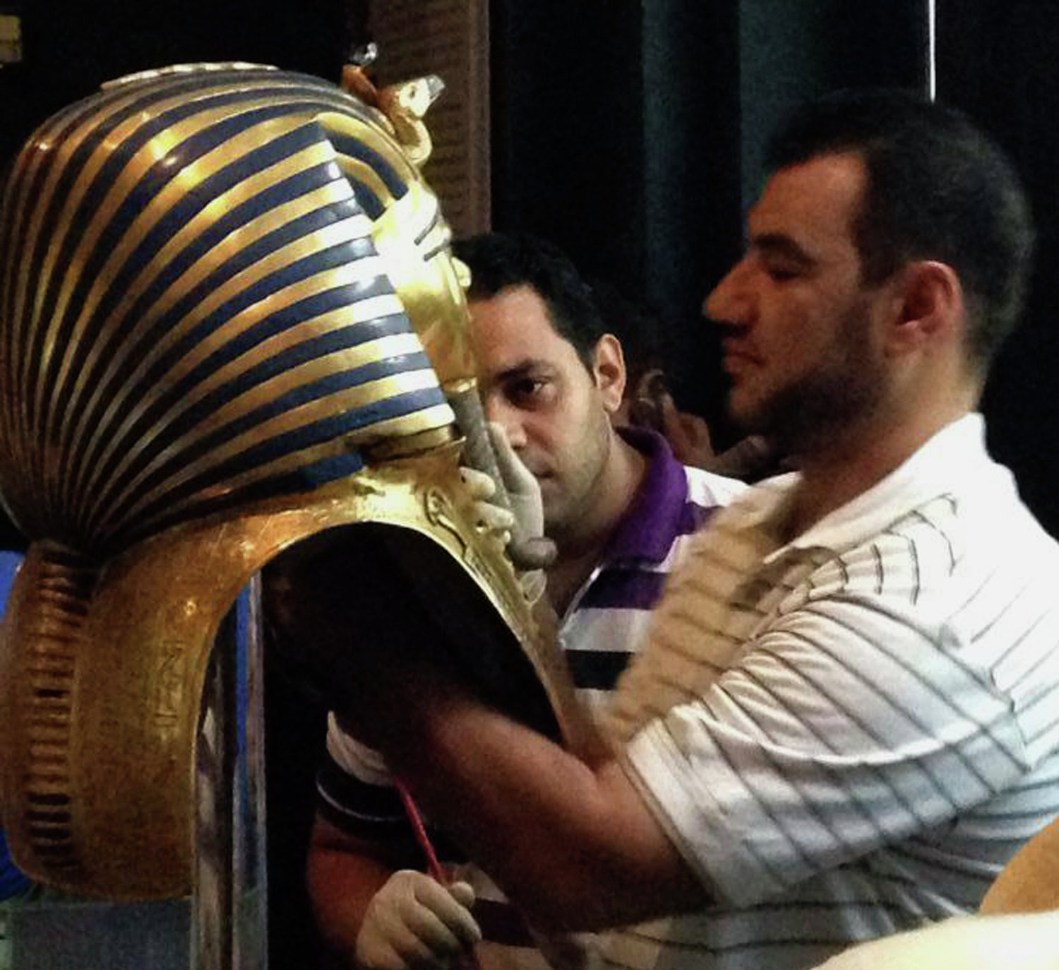 In this Aug. 12, 2014, photo provided by Jacqueline Rodriguez, a man glues the beard part of King Tutankhamun's mask back on at the Egyptian Museum in Cairo, Egypt