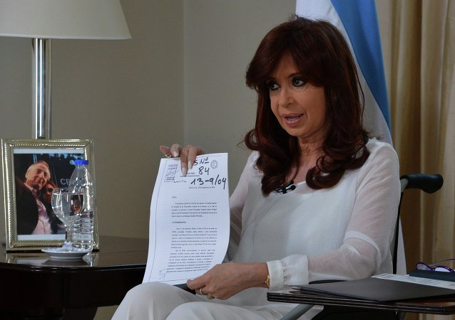 Argentina's President Cristina Fernandez de Kirchner shows a document as she addresses the nation during a televised speech in Buenos Aires