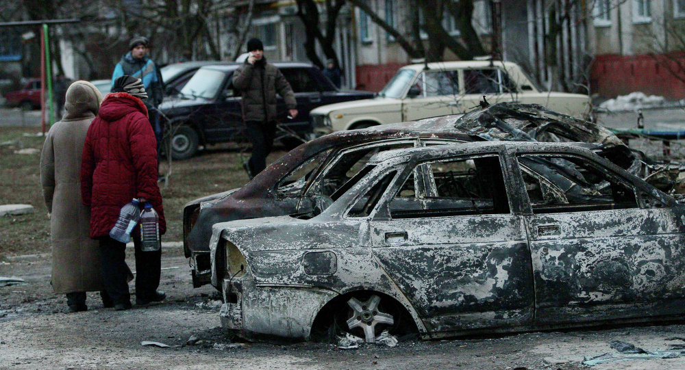People look at burned out cars as they walk along a street in the southern Ukrainian city of Mariupol