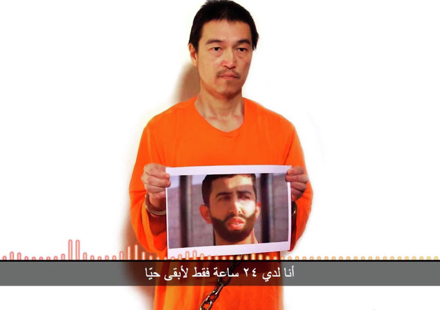 Kenji Goto holding what appears to be a photo of Jordanian army pilot Muath al-Kaseasbeh
