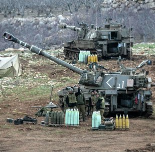 Israeli soldiers stand next to a mobile artillery unit near the border with Syria in the Golan Heights January 28, 2015.