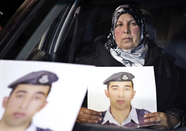 In this Tuesday, Jan. 27, 2015 photo, a woman holds a picture of her son, Jordanian pilot Lt. Mu'ath al-Kaseasbeh, who is held by Islamic State group militants, in a car during a sit-in in front of the cabinet offices in Amman calling for his release, hours after militants posted a video purporting to show a Japanese hostage holding his picture with a message that both hostages would be killed within 24 hours