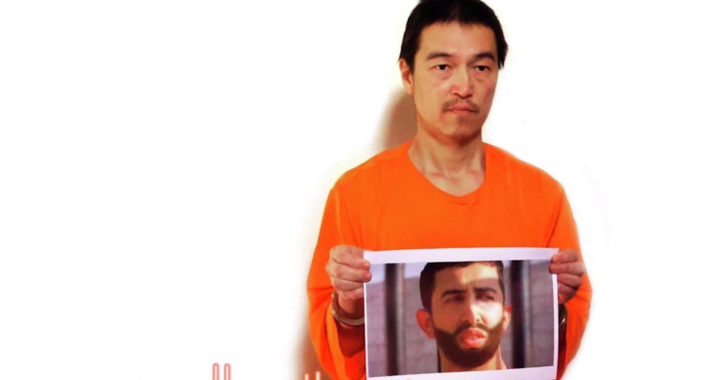 This still image taken from a video posted on YouTube by jihadists on Tuesday, Jan. 27, 2015, shows a still photo of Japanese journalist Kenji Goto holding what appears to be a photo of Jordanian pilot 1st Lt. Mu'ath al-Kaseasbeh