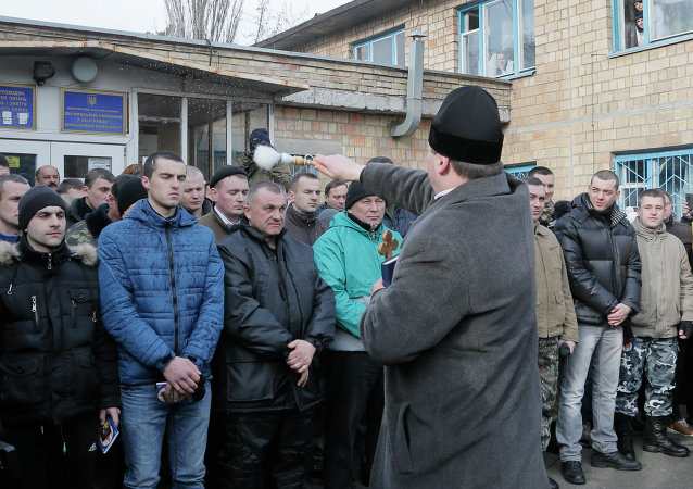 A priest blesses newly mobilized recruits in front of a military registration office before they leave for military units, in Kiev, Ukraine, Thursday, Jan.29, 2015