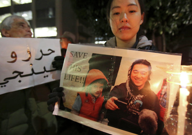 A protester holding a photo of Japanese journalist Kenji Goto who was taken hostage by the Islamic State group