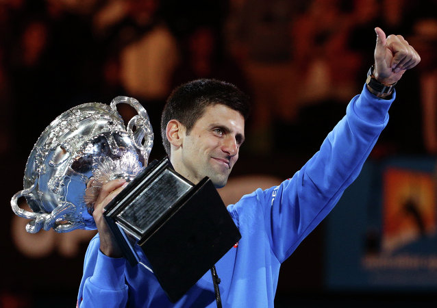 Novak Djokovic of Serbia holds the trophy after defeating Andy Murray of Britain in the men's singles final at the Australian Open tennis championship in Melbourne, Australia, Sunday, Feb. 1, 2015