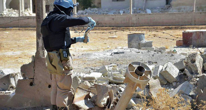 Member of UN investigation team taking samples of sands near a part of a missile that is likely to be one of the chemical rockets according to activists, in Damascus countryside of Ain Terma, Syria